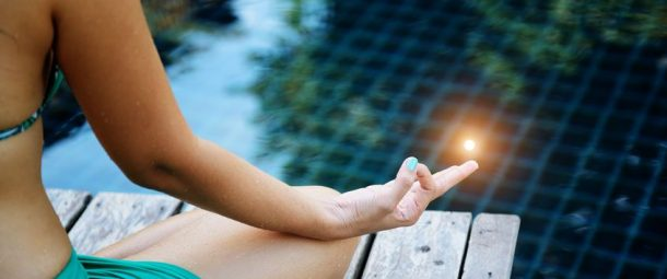 22141865 - woman training yoga and meditation at poolside ,concentrate on finger